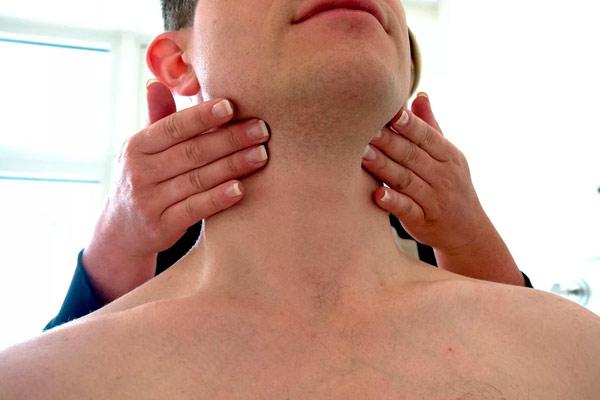 врач изучает жировик сзади на шее